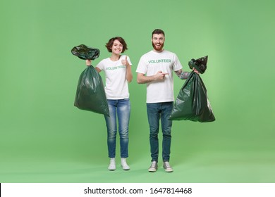 Smiling two young friends couple in volunteer t-shirt isolated on pastel green background. Voluntary free work assistance help charity grace teamwork concept. Pointing on trash bags, showing thumb up