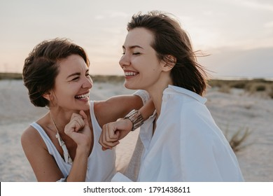 smiling two young women friends having fun on the sunset beach, queer non-binary gender identity, gay lesbian love romance, boho summer vacation style wearing jeans