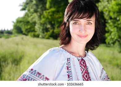 Smiling ukrainian woman outdoors on the summer meadow in traditional shirt