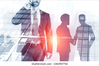 Smiling unrecognizable businessman talking on smartphone over gray skyscraper background. Silhouettes of businessmen shaking hands. Toned image double exposure