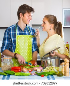 Smiling vegetarian couple cooking healthy dinner together at home kitchen