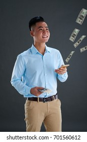 Smiling Vietnamese man using banking application on his smartphone