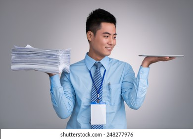 Smiling Vietnamese manager with pile of documents in one hand and digital tablet in another