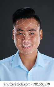 Smiling Vietnamese young man with face marked for 3D modeling
