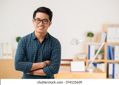 Smiling Vietnamese young man in glasses looking at camera