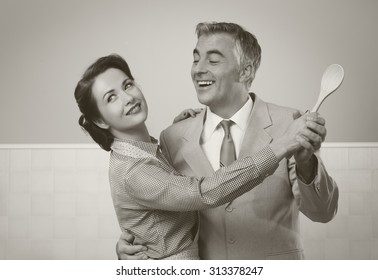 Smiling vintage couple dancing in the kitchen and holding a wooden spoon