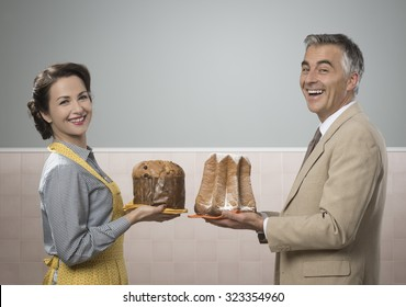 Smiling vintage couple at home holding home made panettone and pandoro