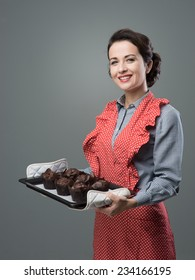 Smiling vintage woman holding a baking tray with chocolate home made muffins