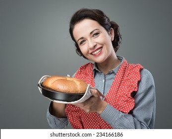Smiling vintage woman holding an homemade cake in a baking tin