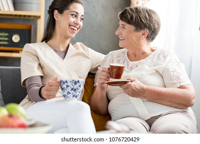 Smiling volunteer drinking coffee with a senior patient in a nursing home