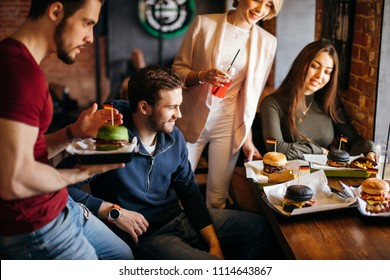 smiling waiter bringing ordered burgers Polite young waiter bringing ordered dishes to guests at restaurant