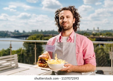 Smiling waiter. Friendly smiling waiter feeling excited while bringing fast food order for his visitors