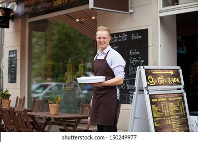 Smiling waiter in front of the sidewalk cafe
