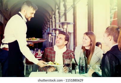 Smiling waiter serving guests at terrace restaurant