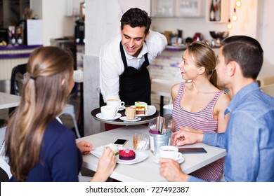 Smiling waiter showing hospitality and serving visitors in cozy coffeehouse