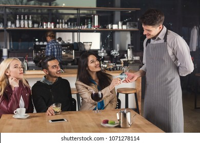 Smiling waiter taking credit card from customer to pay for beverage at coffee shop counter. Small business, occupation people, payment and service concept, copy space
