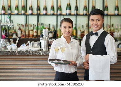 Smiling waiter and waitress with drinks and towel
