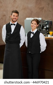 Smiling waiter and waitress in uniform in a restaurant
