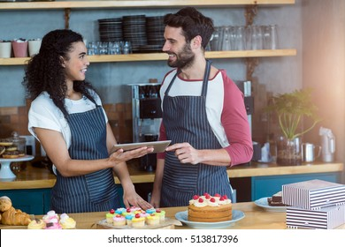 Smiling waiter and waitress using digital tablet at counter in café