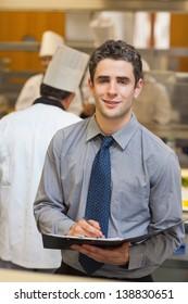 Smiling waiter writing in folder in kitchen
