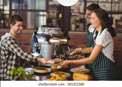 Smiling waiters serving a client at the coffee shop
