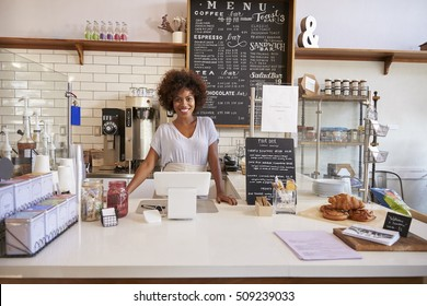 Smiling waitress behind the counter at a coffee shop