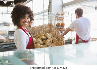 Smiling waitress carrying basket of bread at the bakery