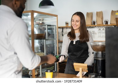 Smiling waitress giving pos payment terminal to african-american customer, back view a guy is using a contactless method to pay for the order in a cafe, bakery