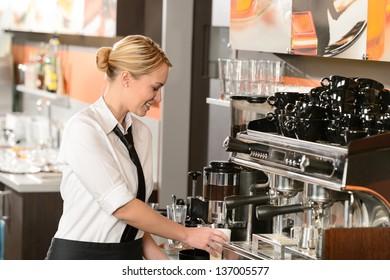 Smiling waitress preparing hot beverage in coffee house
