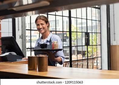 Smiling waitress serving cup of coffee in restaurant. Happy woman holding tray with cappuccino at the coffee shop and preparing bill while looking at camera. Latin woman making cheque for customer.