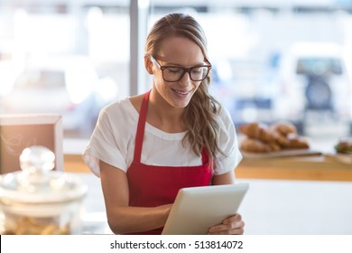 Smiling waitress sitting at table and using digital tablet in cafe