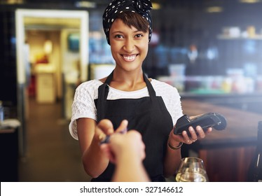 Smiling waitress or small business owner taking a credit card from a customer to process through the banking machine in payment for an order
