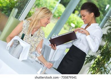 smiling waitress taking order in restaurant