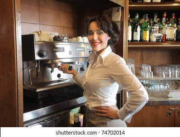 Smiling waitress using a coffee machine in a bar