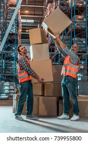 smiling warehouse workers holding stacked boxes and looking at camera