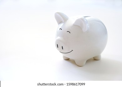 Smiling White ceramic piggy bank on white background. Concept for money saving plan, or financial accounting