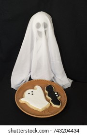 Smiling white ghost behind two homemade cookies, a ghost and bat, on an orange plate against a black background.