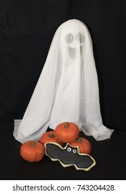 Smiling white ghost, orange clay pumpkins, and a homemade bat cookie against a black background.
