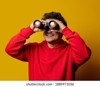 Smiling white guy in rd hoodie with binocular on yellow background