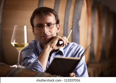 Smiling winemaker in cellar looking satisfied at a glass of white wine during wine tasting, with notebook and pen in hands.