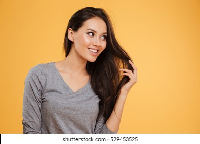 Smiling womam in studio looking away. isolated orange background