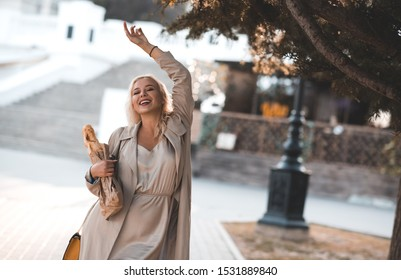 Smiling woman 20-24 year old holding fresh bread walking on streets in city background. Looking at camera. Happiness. 20s.