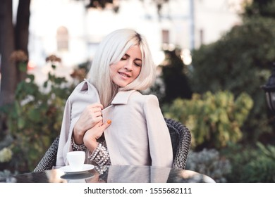 Smiling woman 20-24 year old wearing dress and jacket sitting in cafe drinking coffee outdoors. Good morning. Breakfast. 20s.