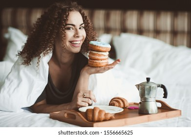 Smiling woman 20-24 year old eating tasty donuts with coffee lying in bed closeup. Good morning. Breakfast time. 20s.