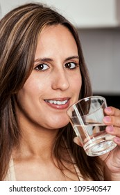 Smiling Woman about to drink a glass of water