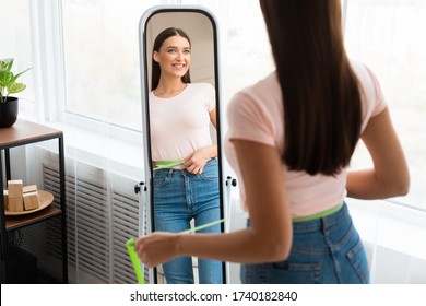 Smiling Woman After Weight Loss Measuring Waist With Tape Standing In Front Of Mirror At Home. Slimming Concept. Selective Focus
