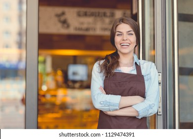 Smiling woman in an apron in the bakery