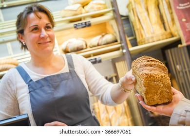 smiling woman with an apron selling bread in a bakery
