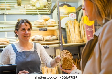 smiling woman with an apron selling bread to a client