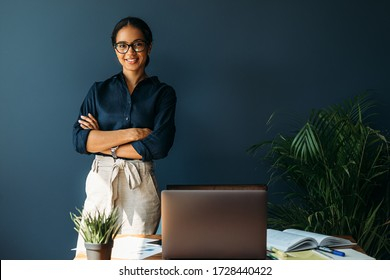 Smiling woman with arms crossed stands at her workplace in home office